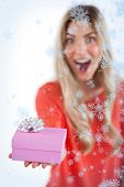 Composite image of Astonished woman holding a gift with snow falling