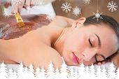 Attractive woman receiving chocolate back mask at spa center against fir tree forest and snowflakes