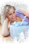 Cheerful blond woman holding a present lying on the floor against christmas frame