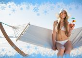 Smiling blonde wearing sunhat sitting on hammock with cocktail against snow flake frame in blue