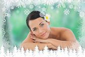 Beautiful brunette relaxing on massage table smiling at camera against fir tree forest and snowflakes