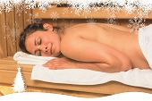 Happy brunette lying down in a sauna against fir tree forest and snowflakes