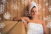 Calm woman relaxing in a sauna against snowflakes