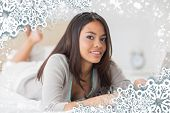 Pretty girl lying on bed using her laptop smiling at camera against snow