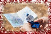 Hiker holding his compass and map in the countryside against snow