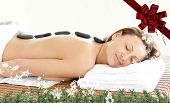 Radiant woman with hot stones on her back against red christmas bow and ribbon
