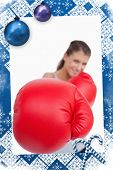 Portrait of a smiling woman boxing against christmas frame