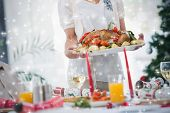 Composite image of Woman bringing roast chicken at table against snow