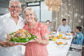 Composite image of Grandparents holding chicken roast with family at dining table against snow