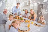 Composite image of Father cutting turkey and looking at camera against snowflakes