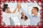 Composite image of casual business team high fiving against snow