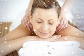 Relaxed woman enjoying a back massage against snow falling