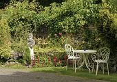 View of English country garden with table and chairs.
