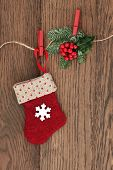 Christmas stocking decoration with holly and fir hanging on a string line over oak background.