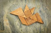 picture of tangram  - abstract picture of a flying bat built from seven tangram wooden pieces over a slate rock background - JPG