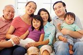 stock photo of multi-generation  - Multi Generation Family Sitting On Sofa At Home Together - JPG