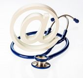 an e-mail sign and a stethoscope on a white background. symbol photo for internet in the doctor's office.