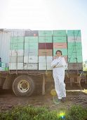 Portrait of female beekeeper with arms crossed standing against truck loaded with honeycomb crates