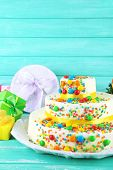 Beautiful tasty birthday cake and gifts on color wooden background