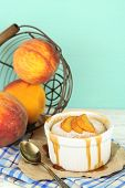 Tasty mini cake with fresh peach, on wooden table