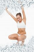 Composite image of Happy attractive woman crouching on a scales with snowflakes on silver