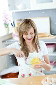 Delighted woman preparing eggs in the kitchen with twinkling stars