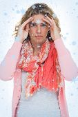 Composite image of Blonde woman touching her temples because of a headache with snow falling