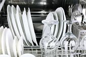 Open dishwasher with clean utensils in it