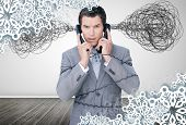 Overworked businessman holding two telephones against snowflake frame