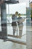 Two business people working with files behind glass of office building