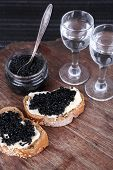Slices of bread with butter and black caviar, glass jar of caviar and pair of small glasses on wooden table on dark background