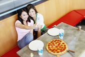 picture of two women taking cell phone  - Two teenage girls taking picture with cell phone at pizza restaurant - JPG