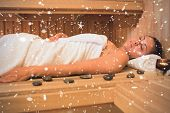 Peaceful brunette woman lying in a sauna against snow falling