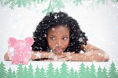 Young woman lying down resting her head on her hands is looking at a piggy bank against frost and fir trees in green