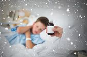Doctor holding cough syrup with boy in hospital against snow falling