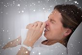 Composite image of side view of sneezing woman against snow
