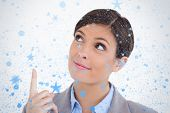 Close up of female entrepreneur pointing and looking up against snow falling