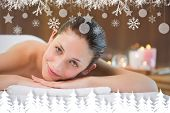 Beautiful woman lying on massage table at spa center against fir tree forest and snowflakes