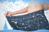 Close up of a woman belly in too big pants against snow flake frame in blue