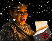 Pretty girl opening a glowing gift against twinkling stars