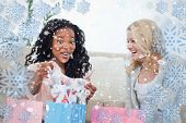 Two laughing women look at clothes they bought against snowflake frame