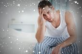 Composite image of depressed man sitting on his bed against snow