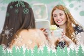 Beautiful young woman receiving a gift box on sofa against snowflakes and fir trees in green