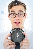 Geeky businessman holding alarm clock against snow falling