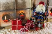 Santa claus with red presents: christmas country style window decoration.