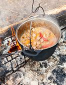 Cooking Goulash soup in cauldron on burning campfire