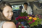 Couple Loading Flowers Into Back Of Suv, Portrait