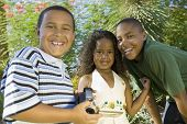 Boy (7-9) holding camcorder with younger sister (5-6) and older brother (10-12) portrait.
