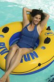 Woman lying on inflatable raft in swimming pool elevated view.