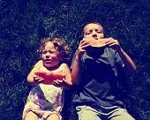 two kids eating watermelon toned with a retro vintage instagram filter effect